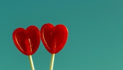 Two lollipops shaped as heart against sky, vintage look
