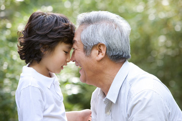 Grandfather with his grandson smiling outdoors
