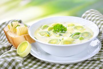 Vegetarische Lauch-Käse-Suppe in weißer  Suppenschale mit Butterbaguette vor softigem  Lauchhintergrund serviert