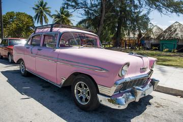 Amerykański zabytkowy różowy samochód na Kubie pod palmami w słoneczny dzień