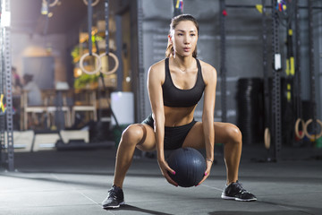 Young woman exercising with medicine ball at gym
