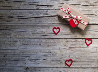 valentine gift box and red heart shape tag on wooden board