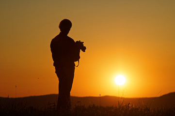 Photographer watching the sunset on a grassy horizon. Silhouette. Forested mountains in the background.