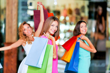 Beautiful young women with bags in shopping center