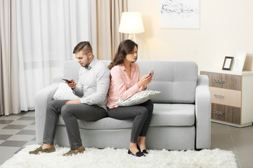 Young couple with mobile phones at home