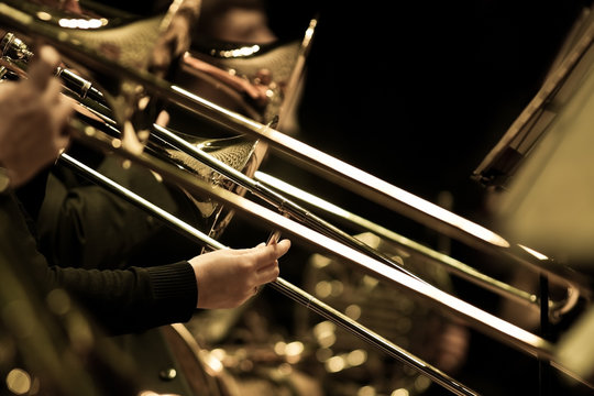 Hands of man playing the trombone in the orchestra