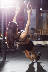 Young woman exercising with gymnastic rings at gym