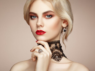 Portrait of beautiful sensual woman with elegant hairstyle.  Perfect makeup. Blonde girl. Fashion photo. Jewelry and lace