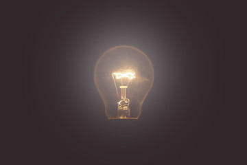 Vintage tone of Light bulb turned on over black background