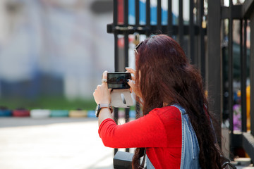 red hair young woman taking photo of beautiful wall with smart phone.