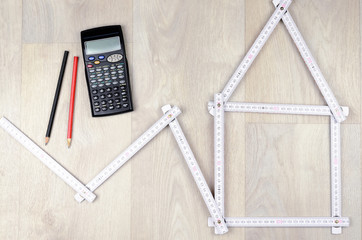 white meter tool forming a house, two pencil and calculator on w