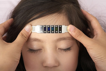 Mother's hands holding temperature strip on daughter's forehead