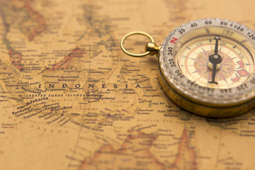 Old compass on vintage map selective focus on Indonesia
