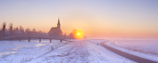 Church and canal in winter at sunrise, Oudendijk, Holland
