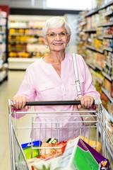 Smiling senior woman pushing trolley