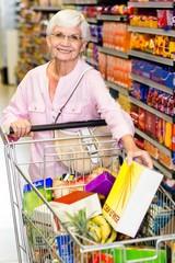 Smiling senior woman taking corn flakes box