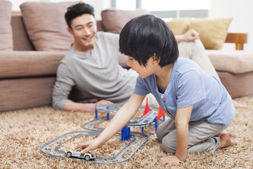 Father and son playing toy car in living room