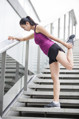 Young woman stretching leg on stairs