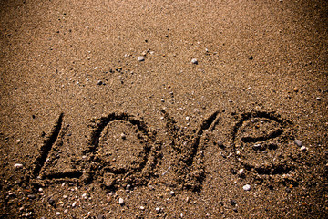 "The inscription ""LOVE"" on a wet sand seacoast. Toned"