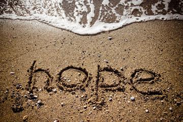"The inscription ""HOPE"" on a wet sand seacoast. Toned"