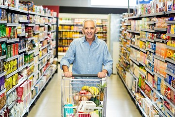 Smiling senior man pushing trolley