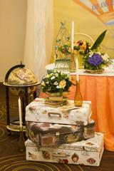 Декоративные чемоданы в стиле ретро, книги, букет и свеча в бутылке