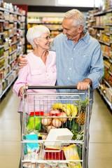 Senior couple embracing while pushing cart