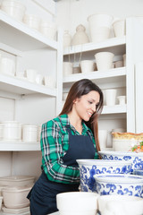 Happy woman working in a ceramics shop