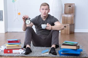 Stressed student holding alarm clock