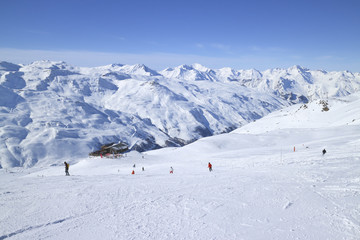 Skiers on ski slopes in high Alps resort, apres ski chalet, with snowy mountain peaks in against blue sky