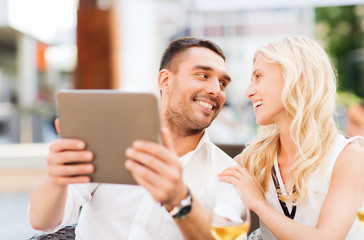 happy couple with tablet pc at restaurant lounge