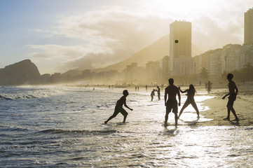 Beach football altinho silhouettes playing in the waves on the shore of Copacabana Beach at sunset in Rio de Janeiro, Brazil