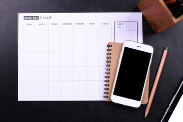 blank screen smartphone with notebook and planner schedule