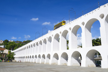 Bonde de Santa Teresa tram train drives along distinctive white arches of the landmark Arcos da Lapa in Centro of Rio de Janeiro Brazil