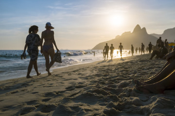 Defocus silhouettes walking along the shore of Ipanema Beach at sunset in Rio de Janeiro, Brazil