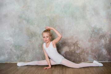 Little ballet dancer doing stretching before class in a white bathing suit, dance, sports, healthy lifestyle, ballet