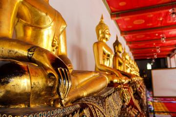 Dettaglio di una serie di statue raffiguranti Buddha al Wat Pho di Bangkok
