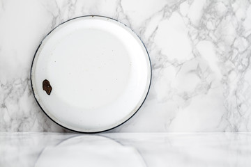 Backside of White Vintage Enamel Plate on Marble