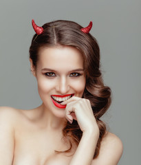 Sensual beautiful model with small horns posing in the studio.
