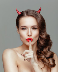 Attractive model with horns posing in the studio.