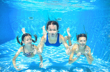 Family swim in pool underwater, happy active mother and children have fun under water