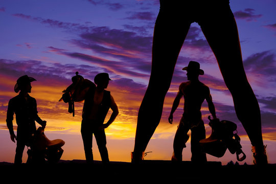 silhouette of woman's legs and three cowboys in the sunset