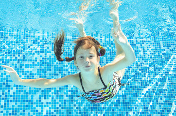 Girl jumps, dives and swims in pool underwater, happy active child has fun under water