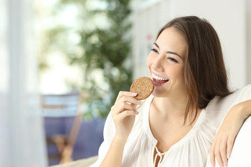 Happy girl eating a dietetic cookie
