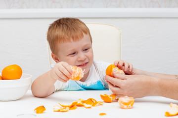 Boy cleans tangerine