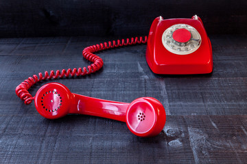 The image represents a vintage red phone on a dark wood background conceptualizing communication or lack thereof