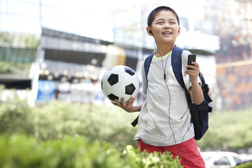 Schoolboy listening to MP3 player with football in hand
