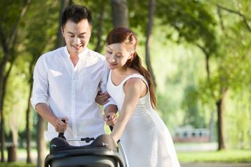 Young couple push a pram
