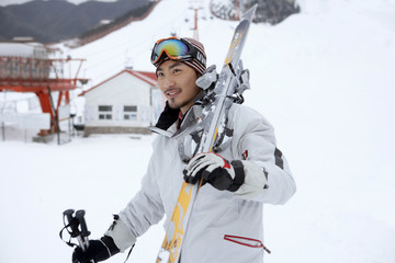 Man On Ski Field, Holding Skis And Poles