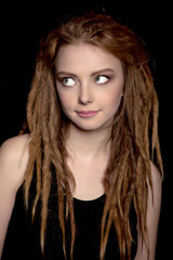 Close-up of beautiful young woman dreadlocks thinking on black background - Stock Image